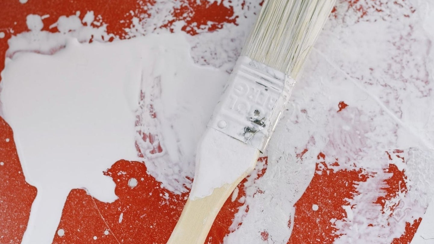 white interior paint and a white paint brush spread over a red paint can lid