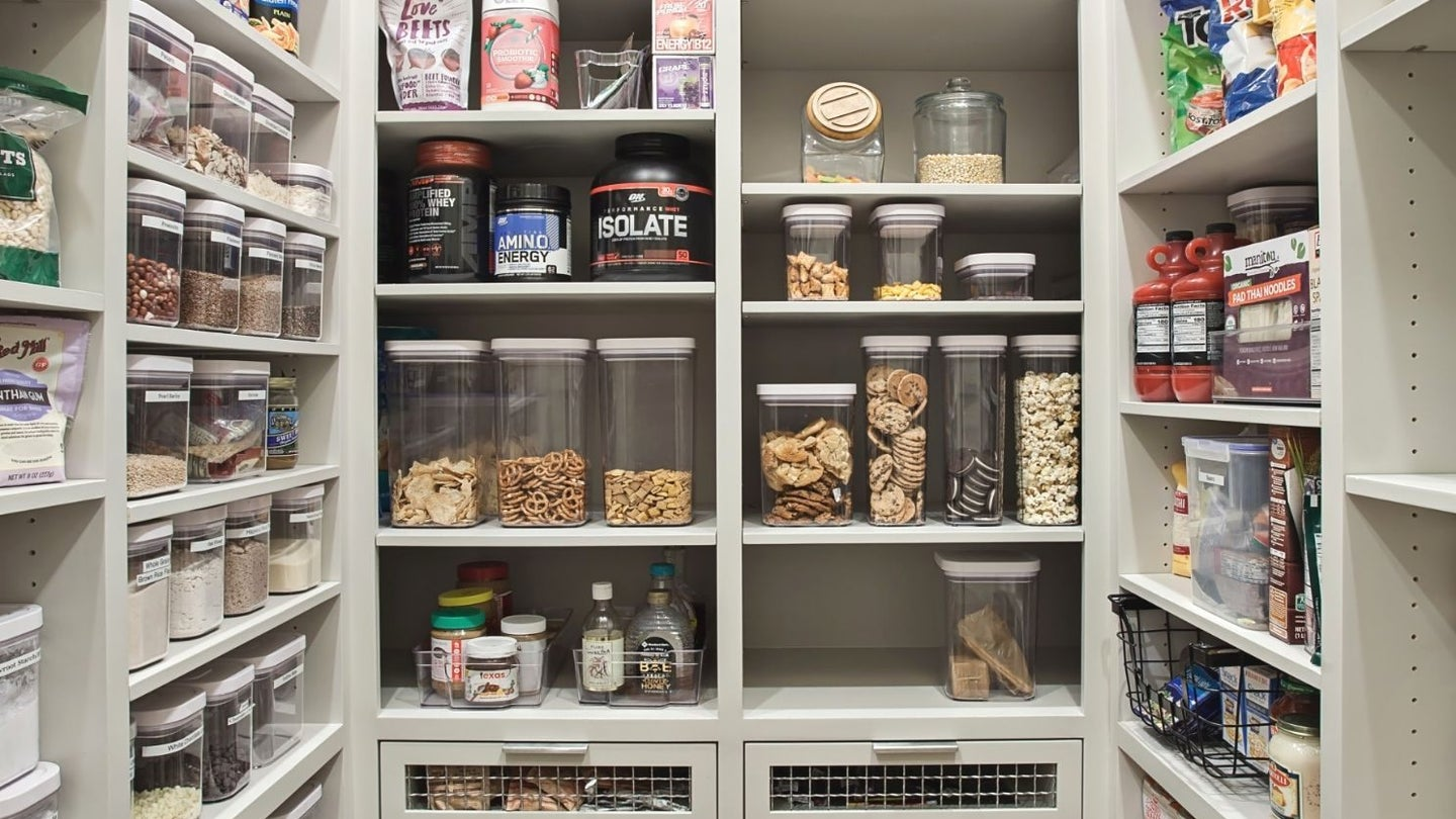 a walk in kitchen pantry stocked with multiple dry good and canned items