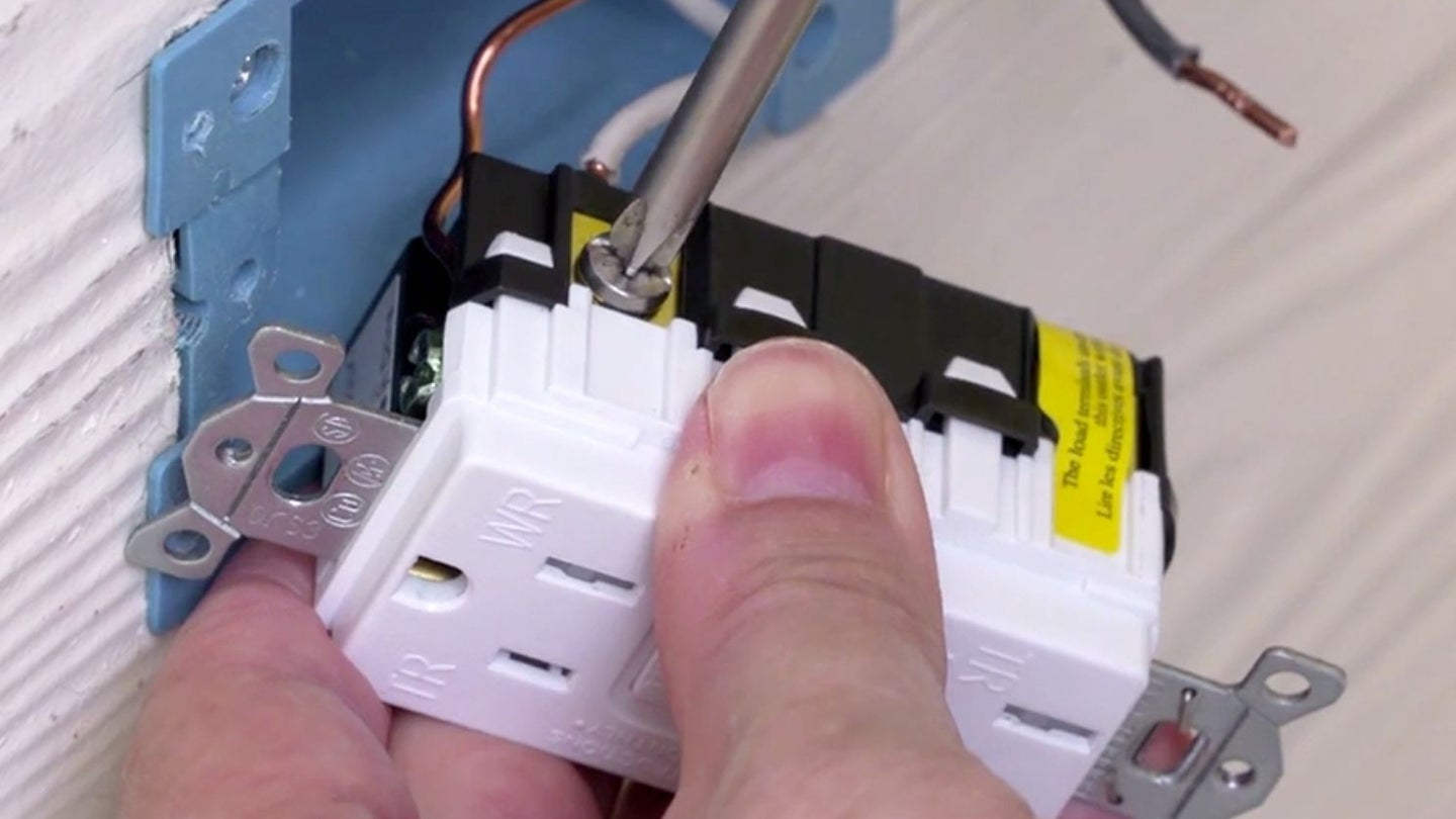 a gfci replacement plug being wired and installed