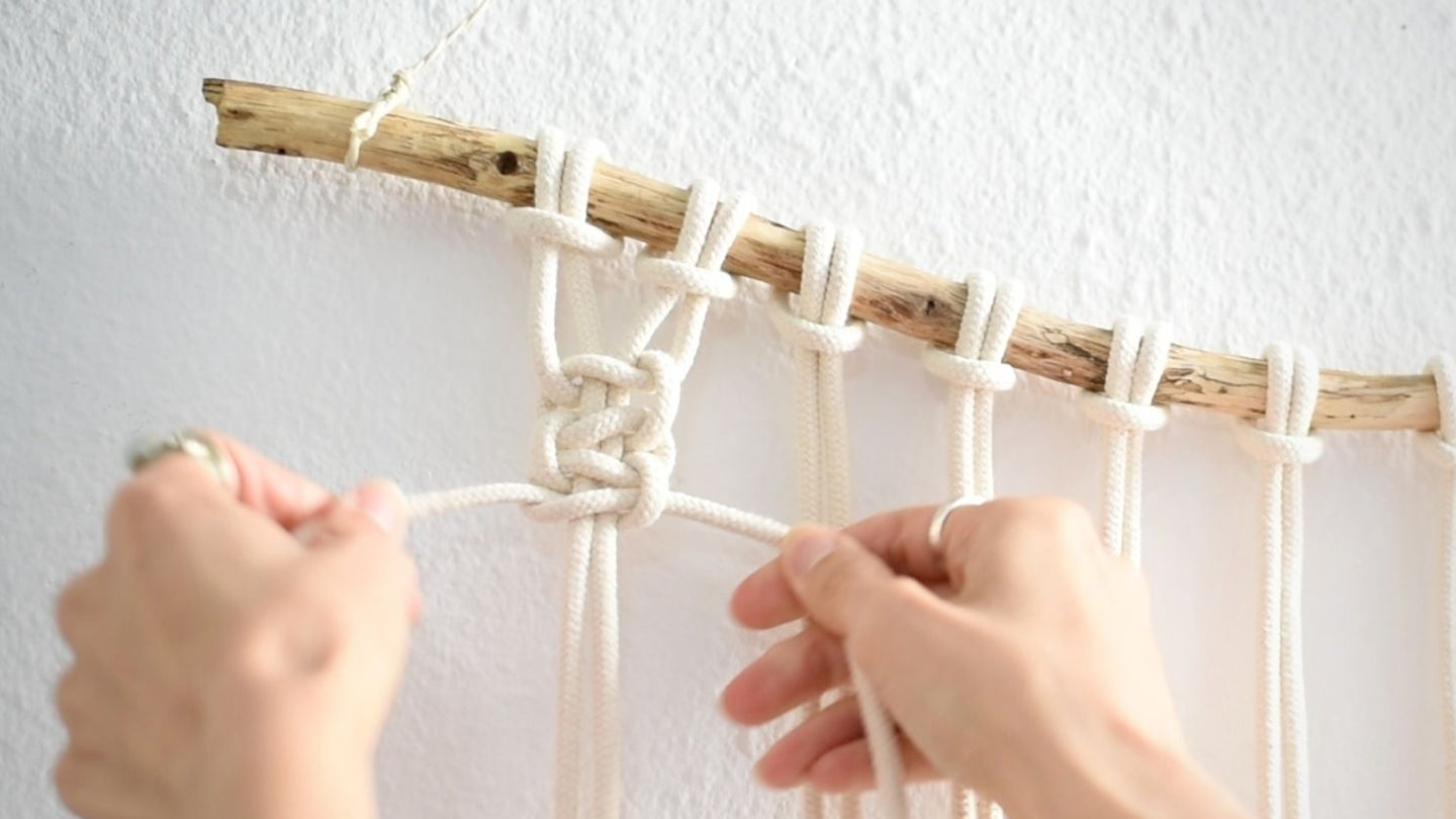 a macrame knot being tied with a macrame cord, hanging from a wooden stick