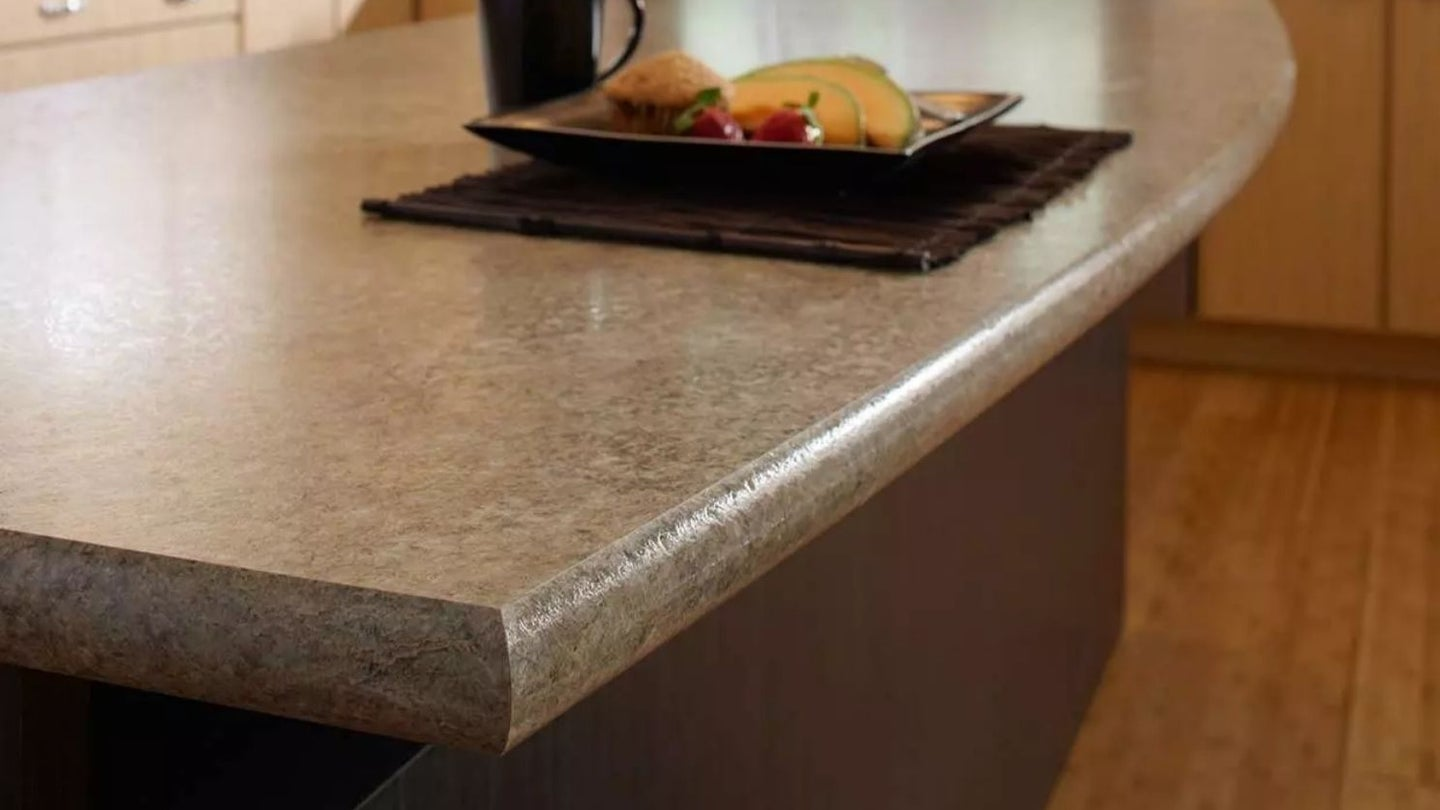 post form laminate kitchen island countertop with a plate of fruit and a coffee sitting on top