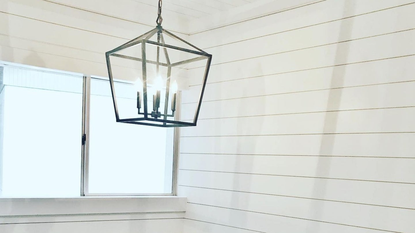 a white room with shiplap walls, a window, and a light hanging from the ceiling