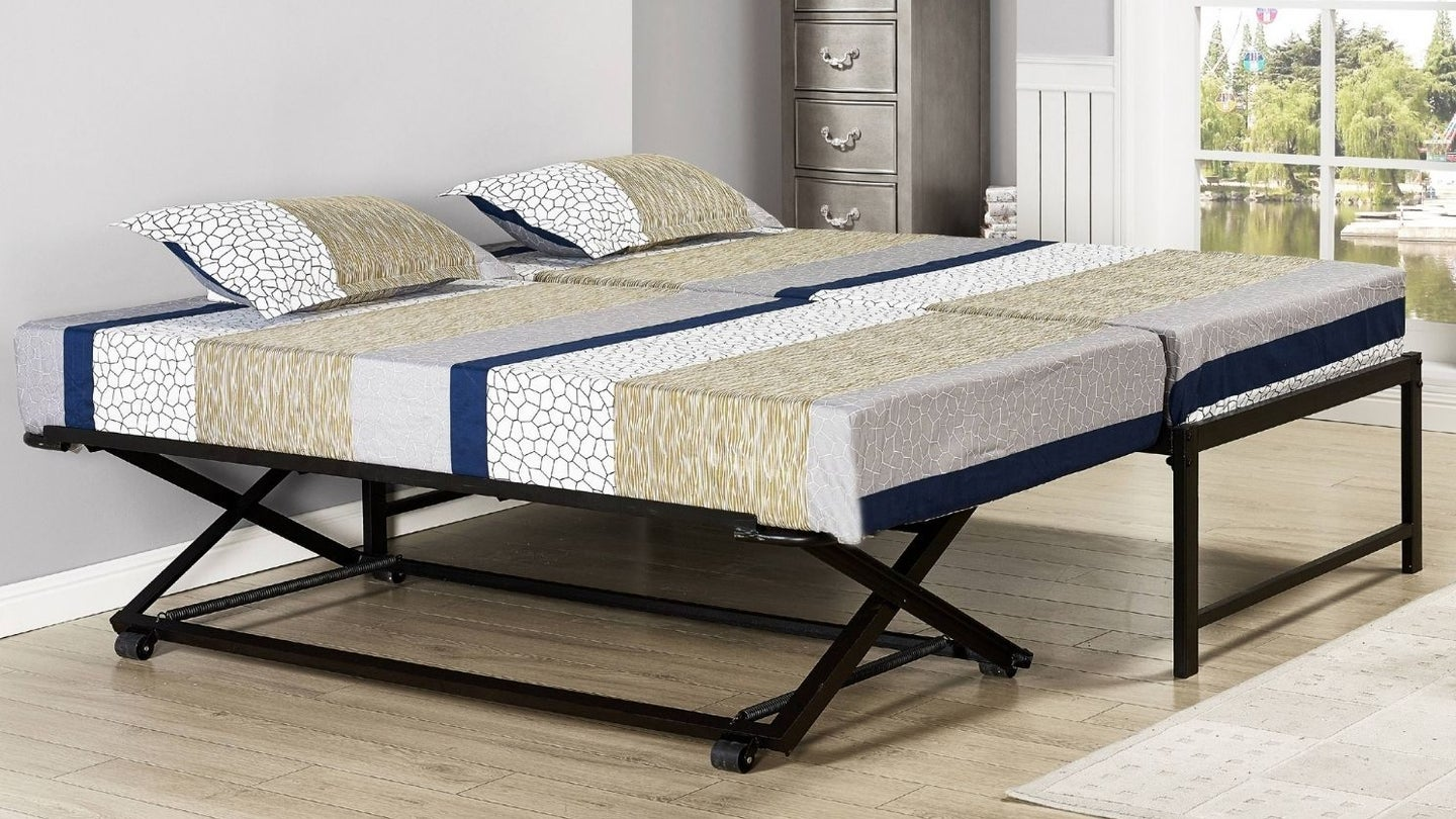 a modern pop up trundle bed set up next to a matching bed.