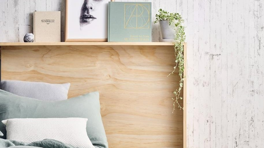 A wooden DIY headboard that doubles as a shelving unit holds pictures and books and sits behind a bed in a bedroom.