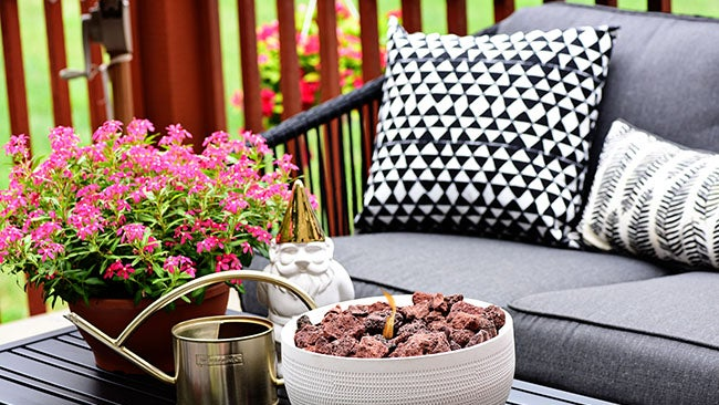 A fire burns inside a miniature tabletop DIY fire bowl on top of an outdoor patio table surrounded by patio furniture.
