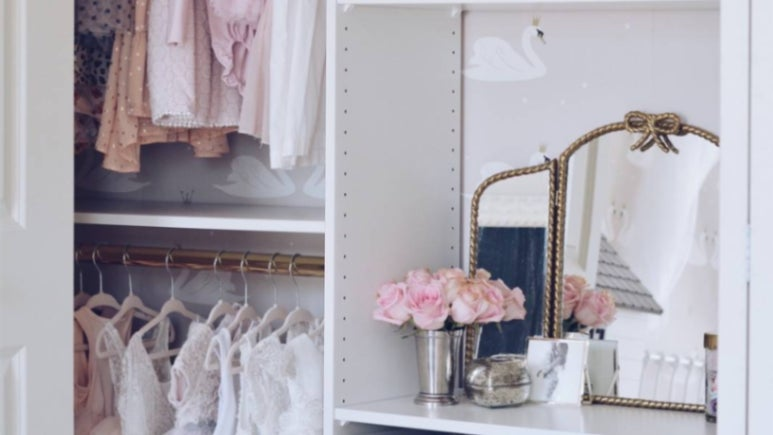 A child's closet with items from Ikea's Pax line in it to establish wardrobe organization in a small bedroom.