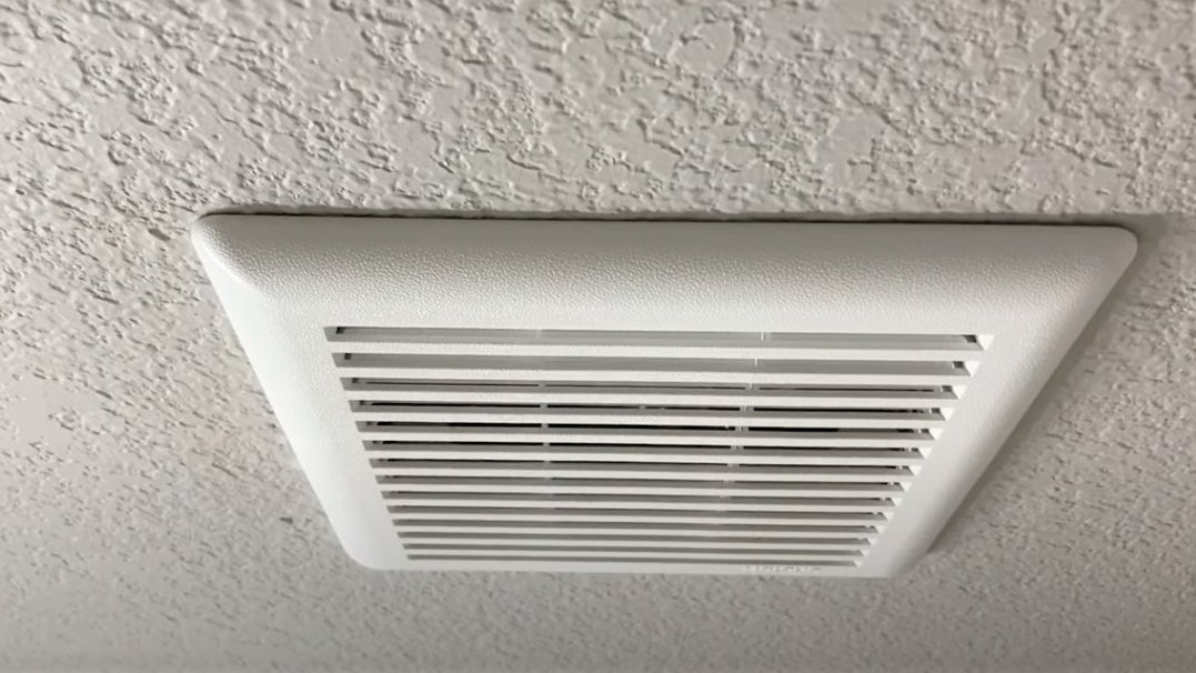A white vent cover for a bathroom ceiling fan is on top of a white-painted textured drywall ceiling.