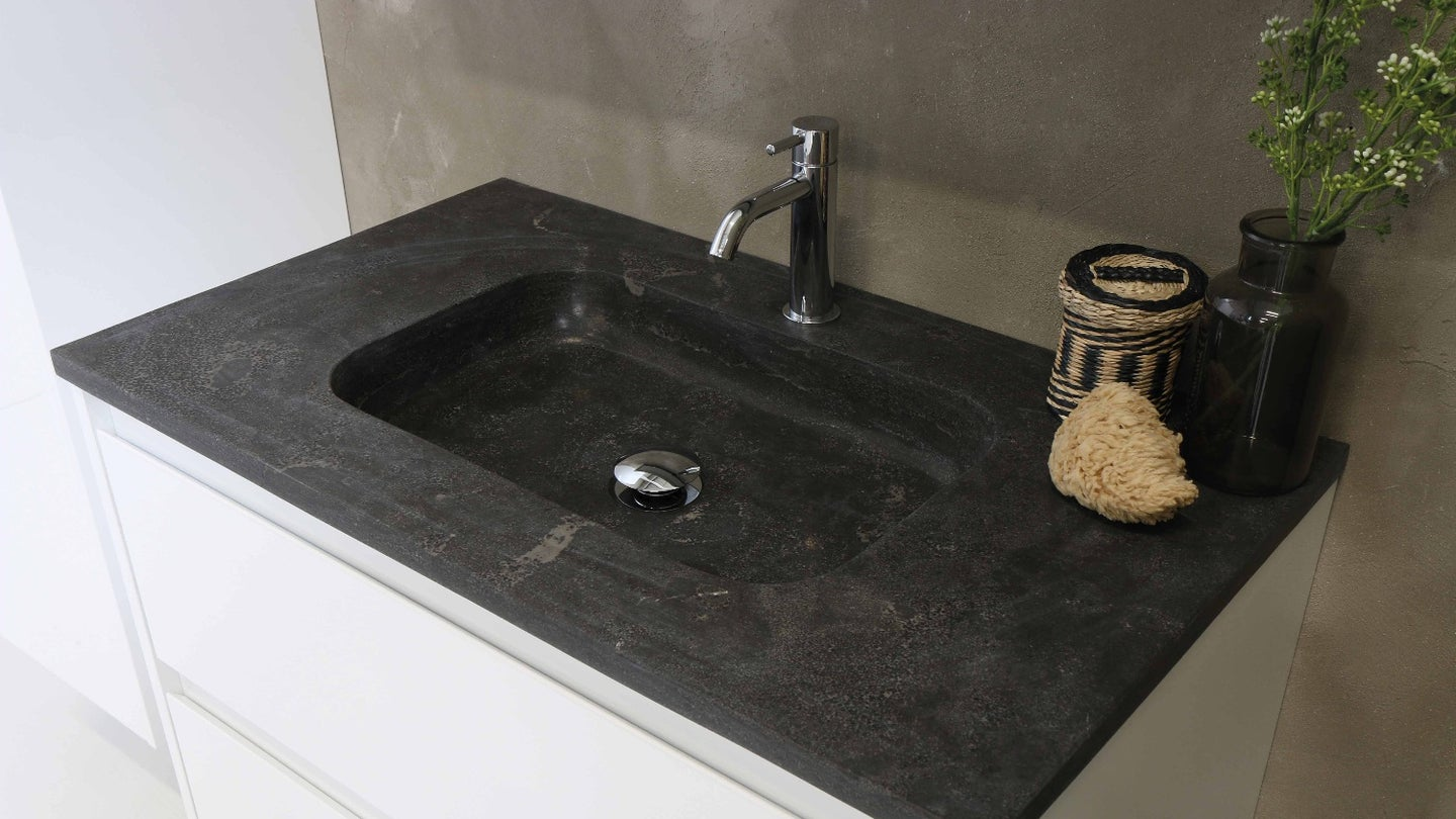 A dark stone bathroom vanity with chrome faucet and white cupboards against a concrete wall in a bathroom.