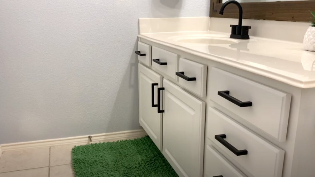 A bathroom that has a vanity with a white countertop, white cabinet doors and drawers, and black metal rectangular hardware.