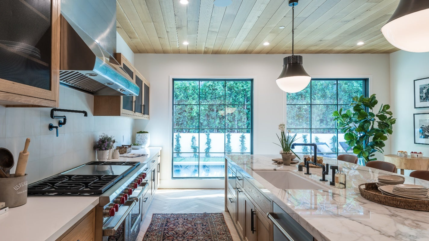 A spacious kitchen with stainless steel appliances, wood and glass storage, marble countertops and island, and large windows.