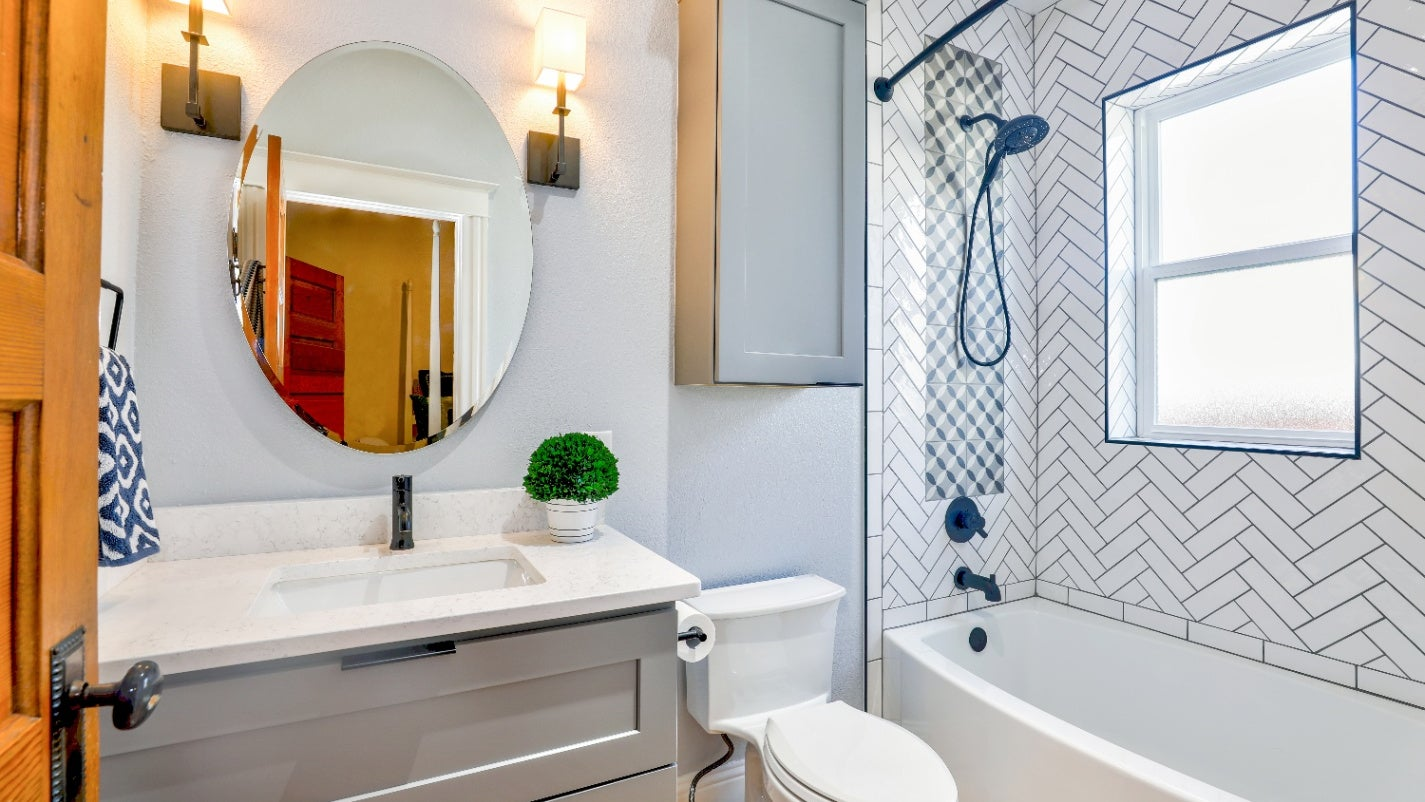 A bright, well-lit bathroom with window, sconces, tub, shower, toilet, mirror, and large bathroom vanity with storage.