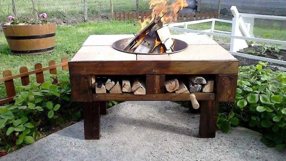 A DIY patio fire pit converted from a wood pallet with firewood storage in a backyard. A fire is burning on top of the unit.