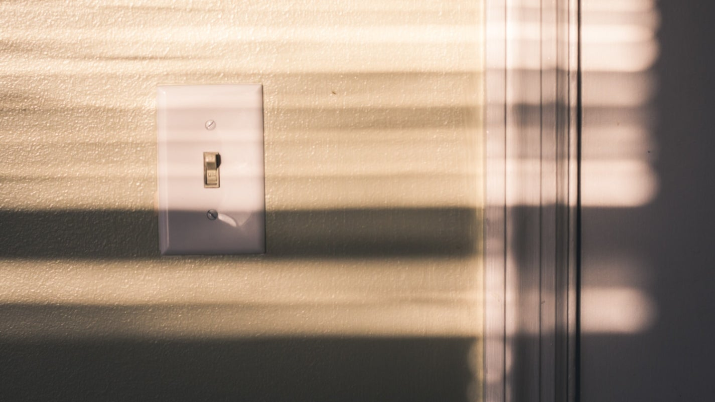 A white toggle-style electrical switch on a sunlit wall.