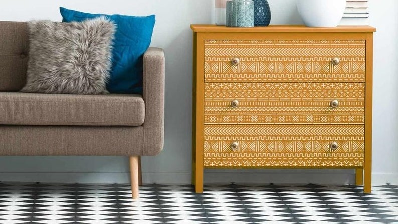 Seating area with beautiful geometric chalk paint patterned yellow cabinet beside a mid-century modern chair and other decor.