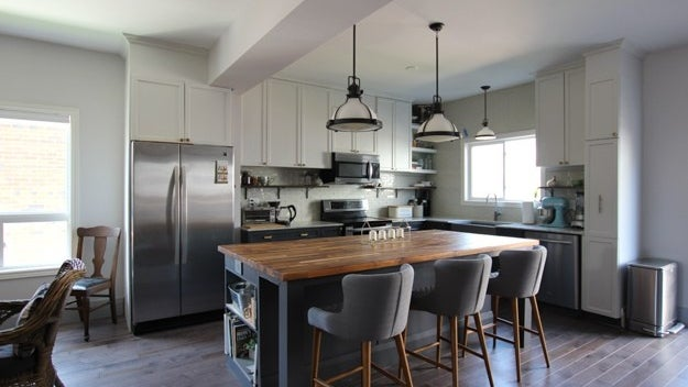 A spacious kitchen with a large, multifunctional, wood-top sit-in kitchen island.