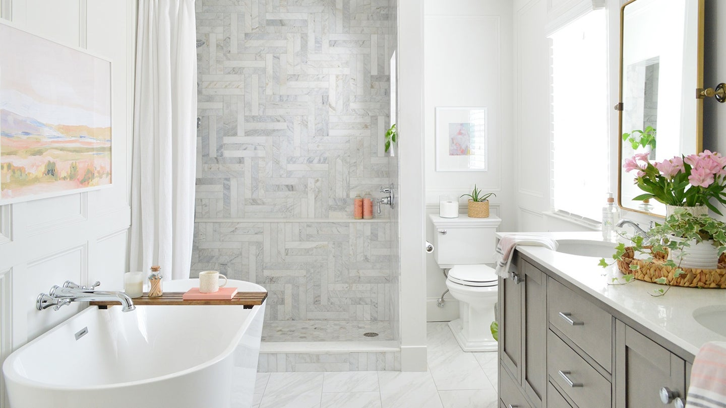 A bright bathroom with a beautifully tiled open-concept walk-in shower with curtain.