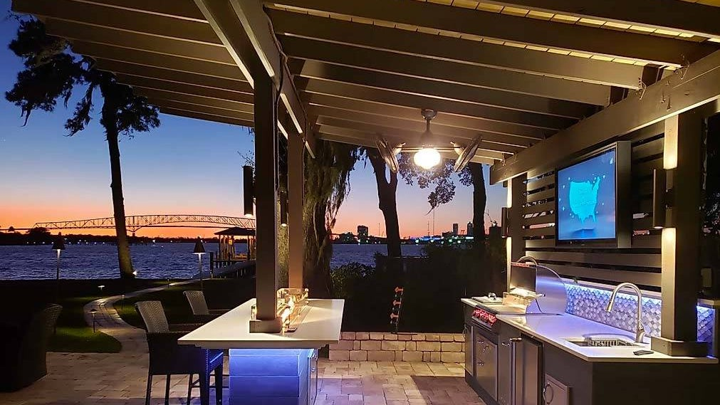 Outdoor patio kitchen with stone countertops, TV, bar/seating area, and wooden pergola in a backyard by a body of water.