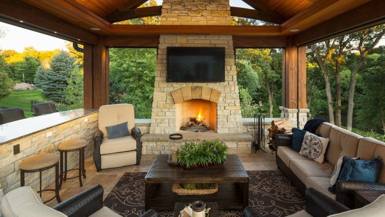 A gorgeous outdoor living room with a fireplace, TV, lots of seating, and a beautiful wood-paneled ceiling in a backyard.