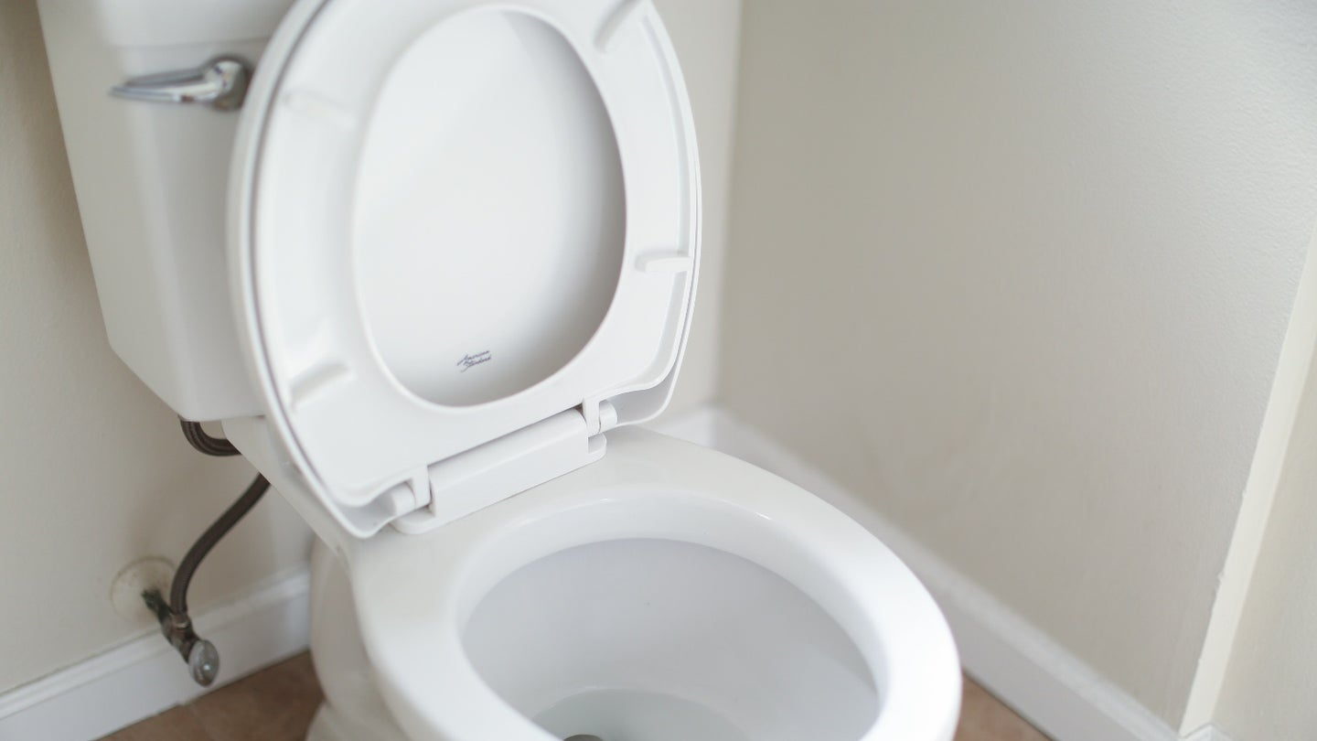A white porcelain toilet with the seat up in a bathroom.
