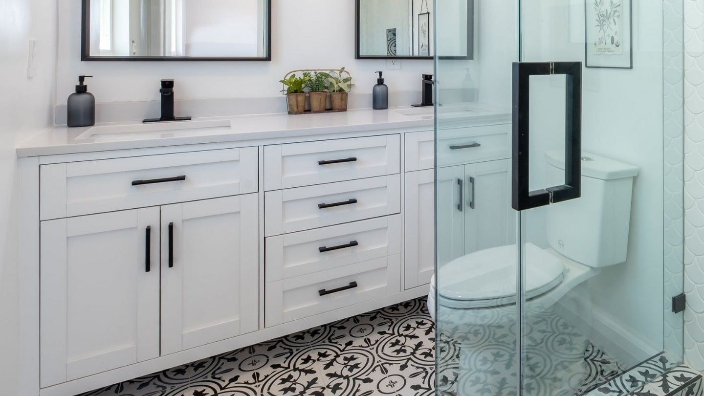 a white bathroom vanity consisting mostly of lower cabinets and a toilet in front