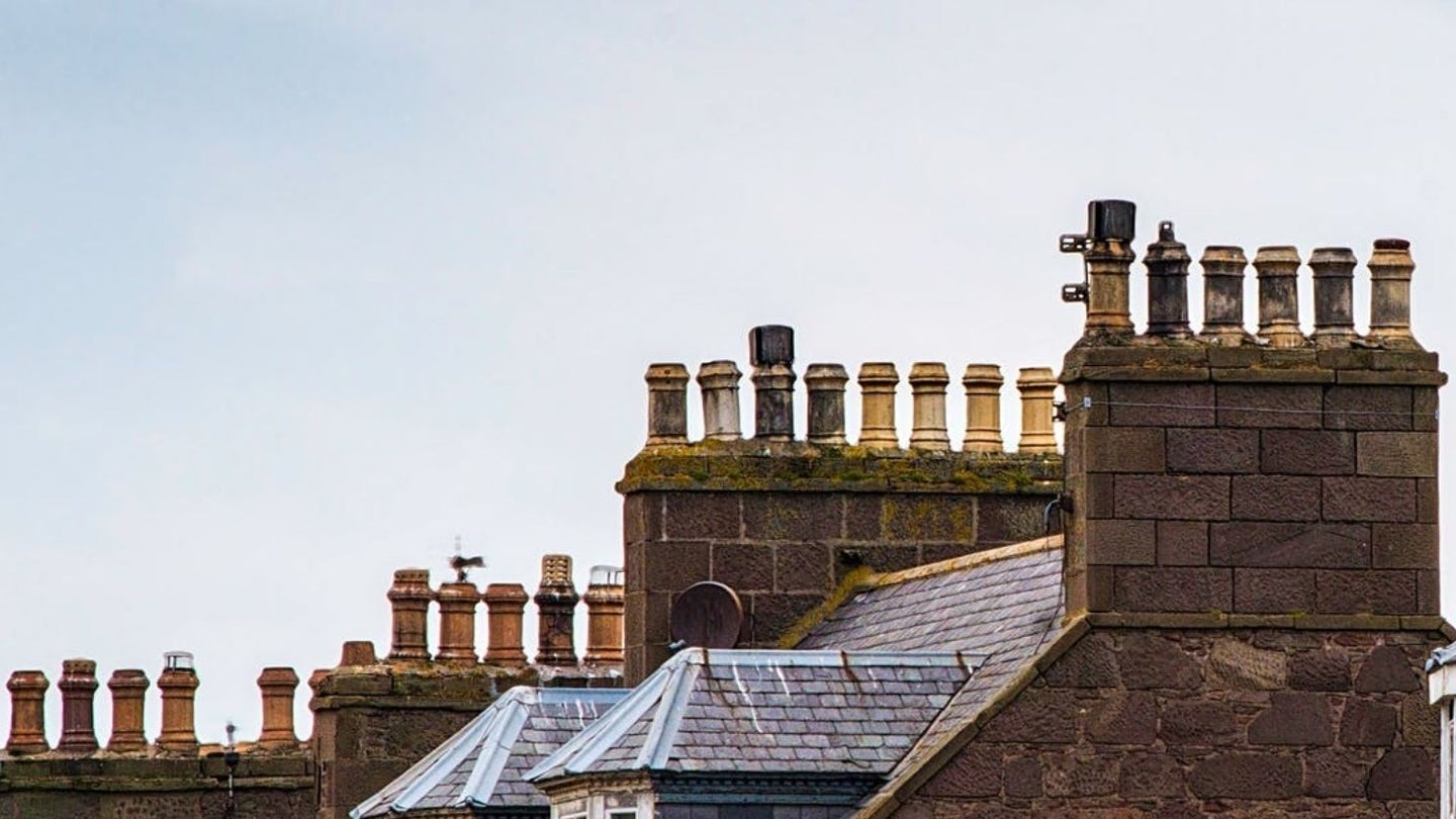 Several chimney flues rising out of a few chimneys along the skyline