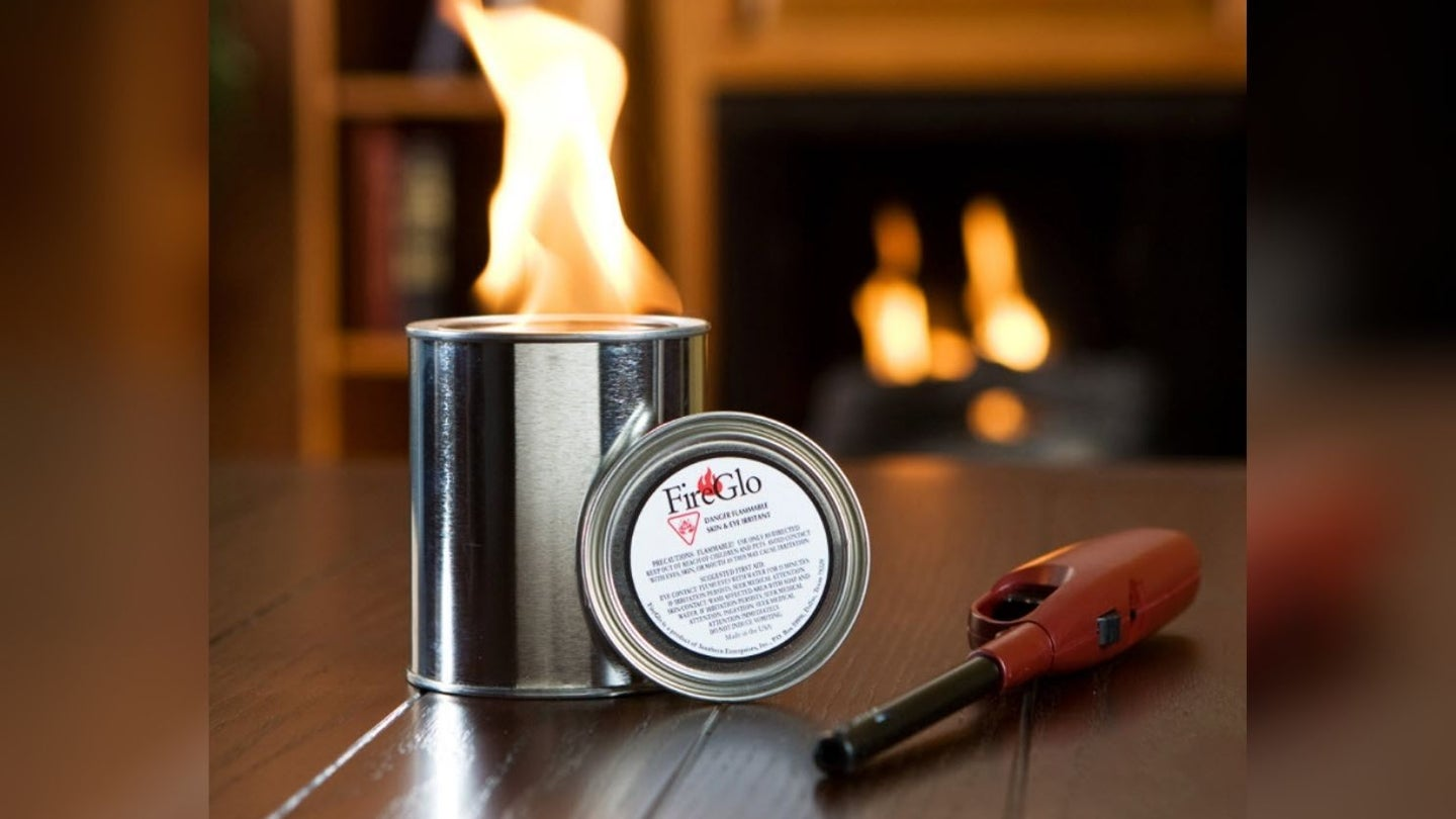 a can of gel fuel burning with a gel fireplace in the background