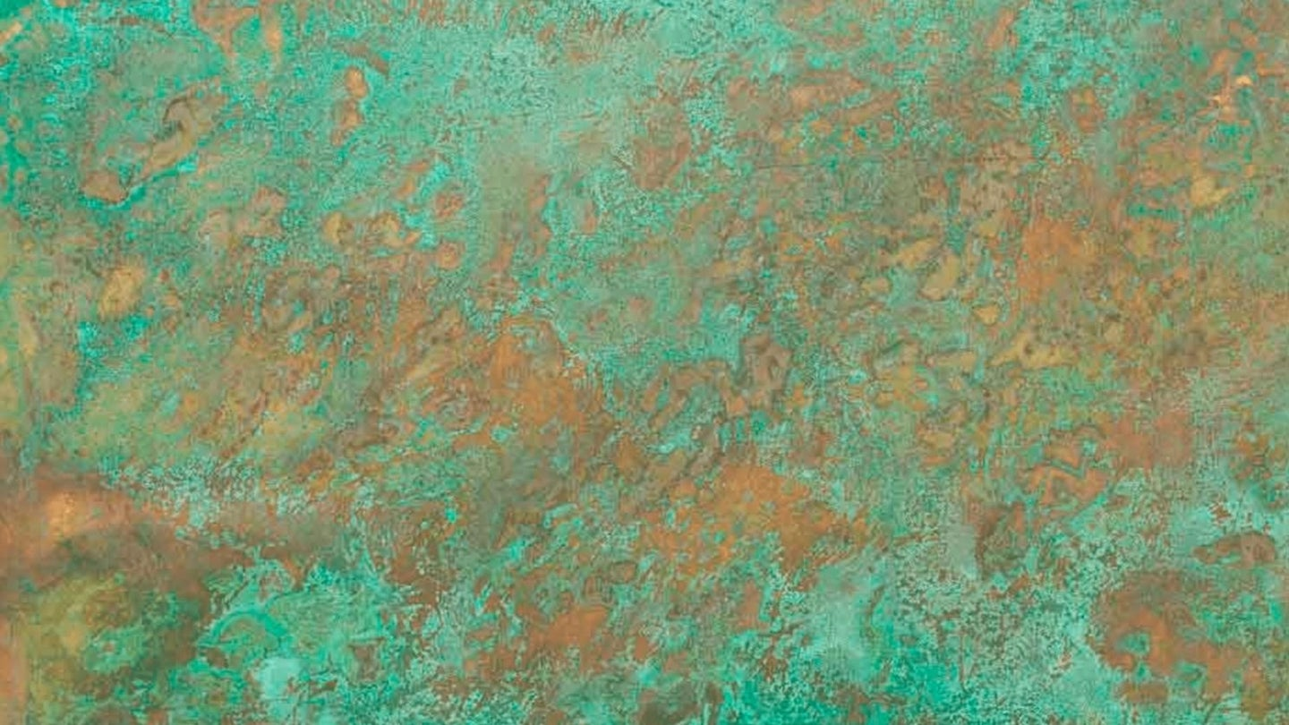 a green and orange patina on a sheet of copper