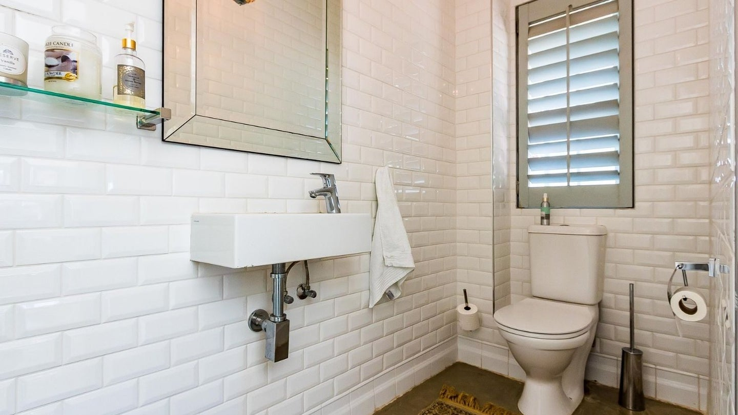 a white two piece powder room, guest bathroom with sink and toilet