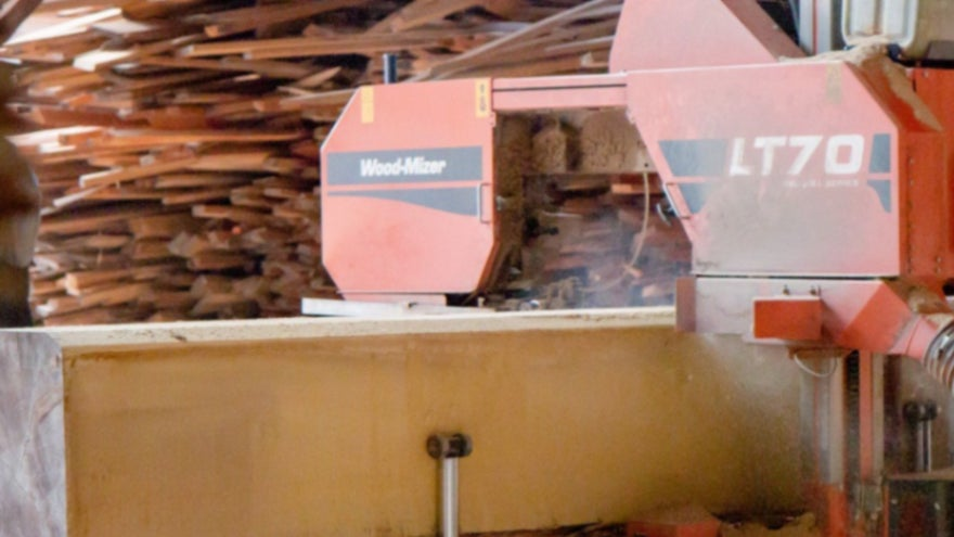 a sawmill cutting up a large beam of wood with stacks of wood in the background.