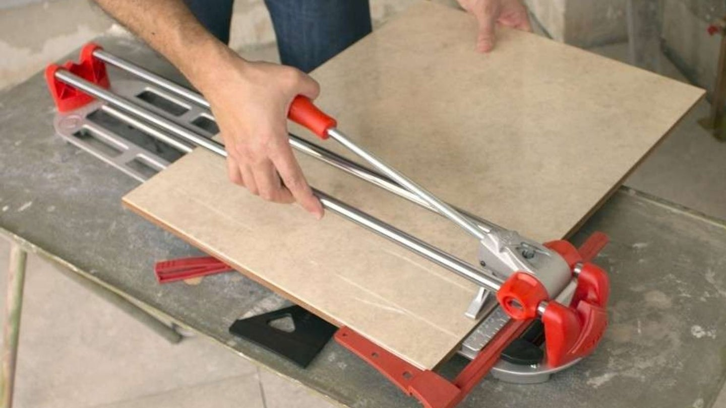 a large tile being cut and snapped in a manual tile cutter