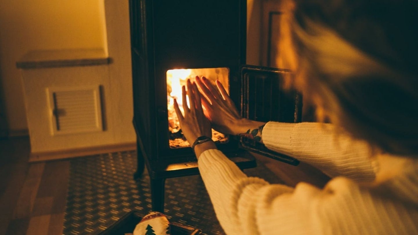 a woman warming her hands by a wood stove