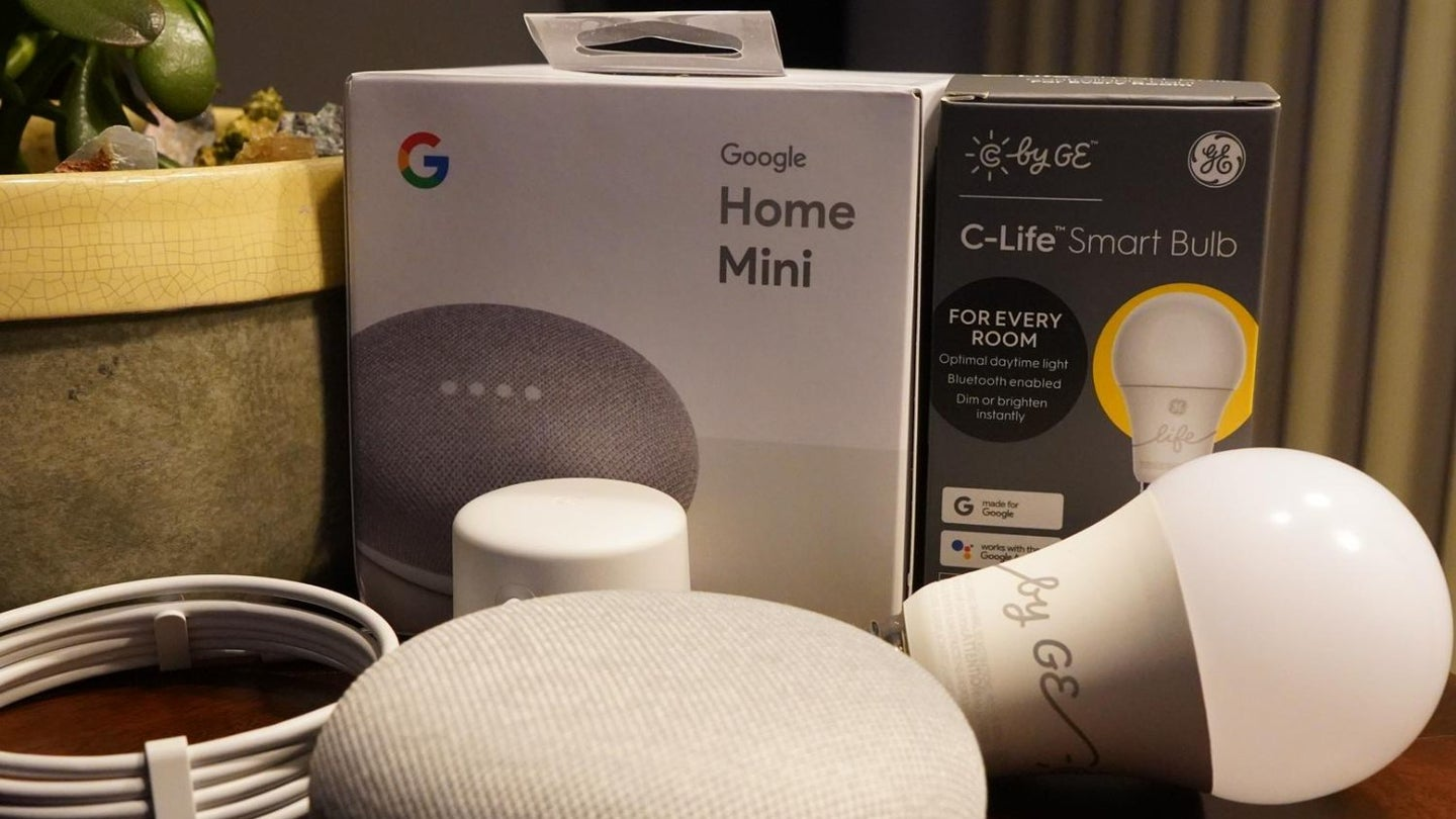 Google mini home and smart bulb rest beside each other on a table