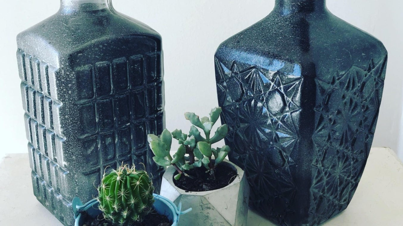 Two decorative glass bottle painted a dark blue and speckled with a soft grey behind two succulents on a table.