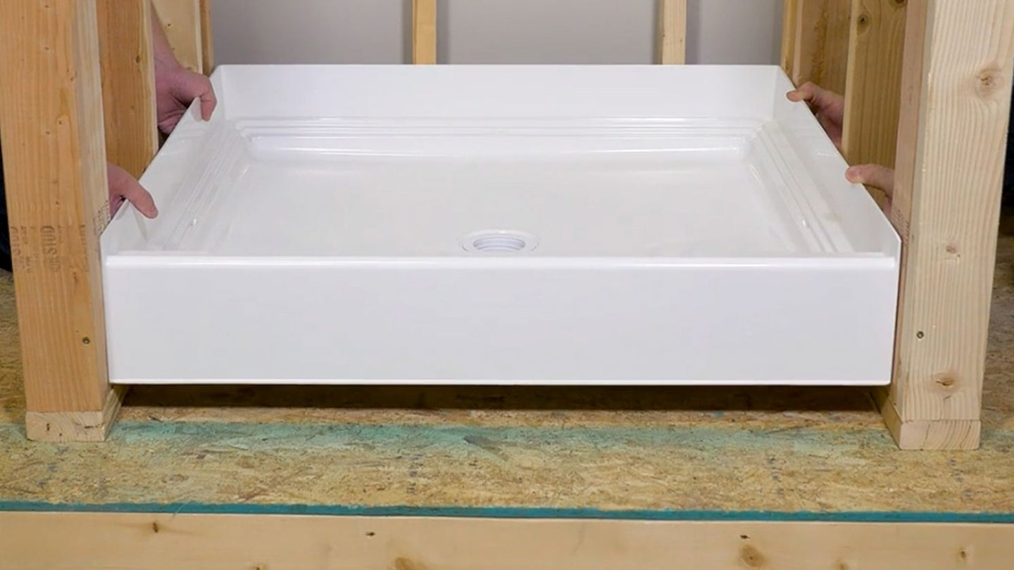 an acrylic shower pan being installed